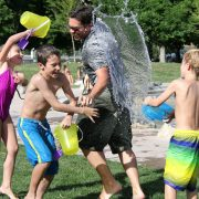 kids splash adult with water at camp