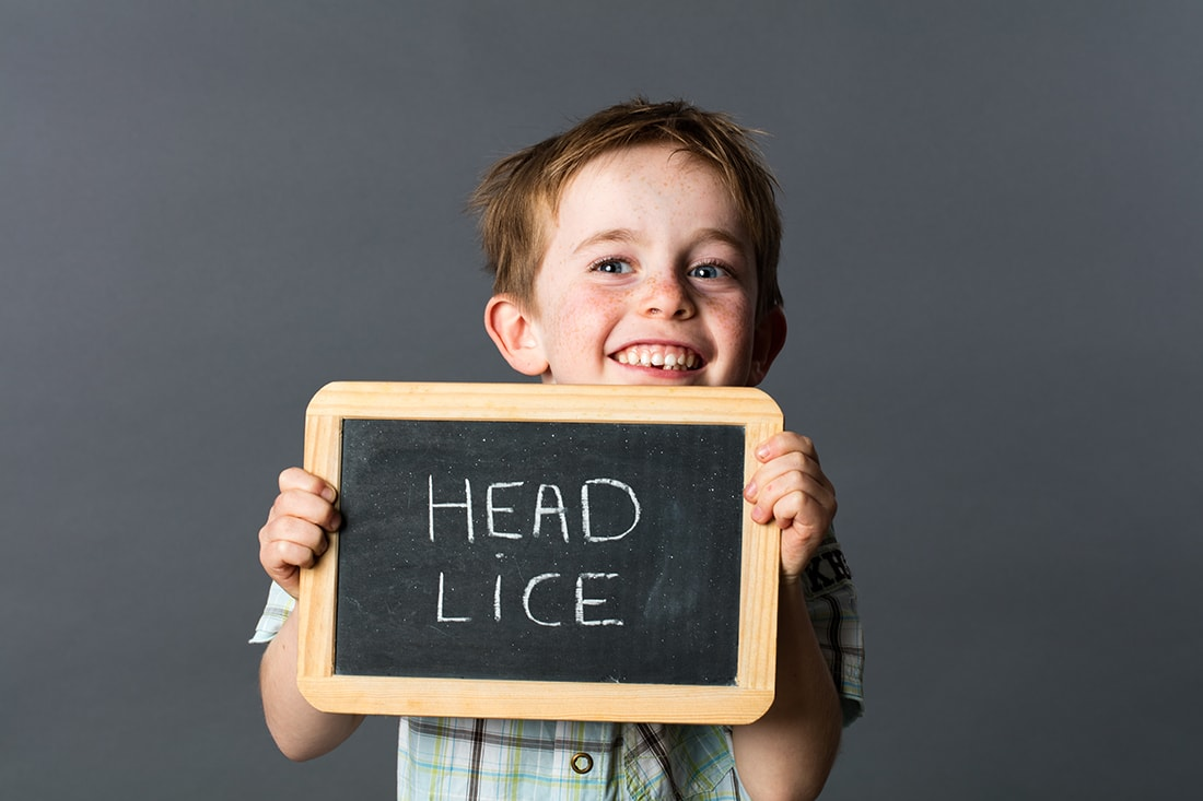 A smiling child holding a head lice sign