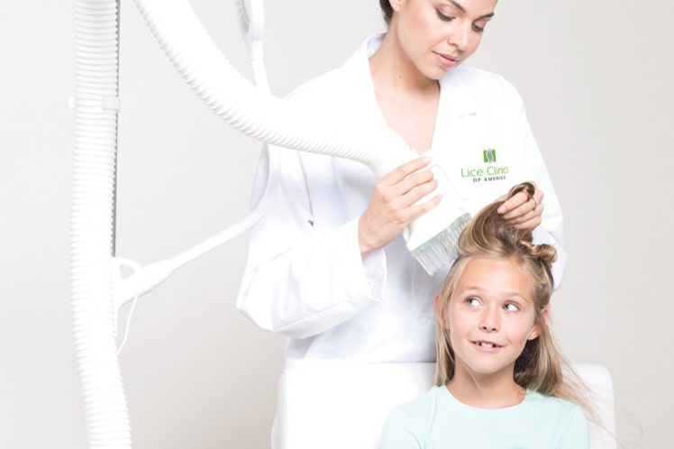 Woman administering AirAlle treatment--one of the fastest ways to get rid of head lice.