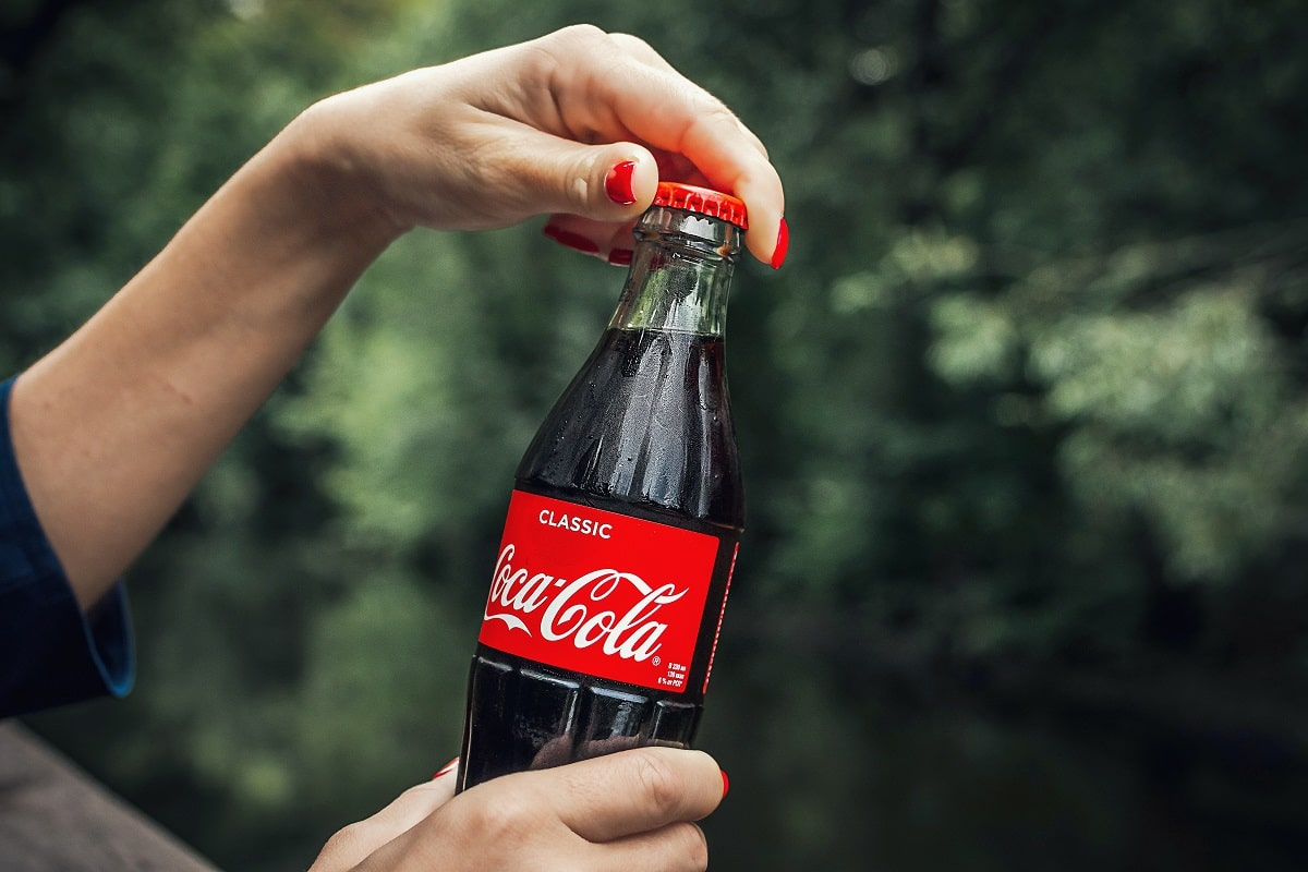 Close up of woman's hands opening a bottle of Coke.