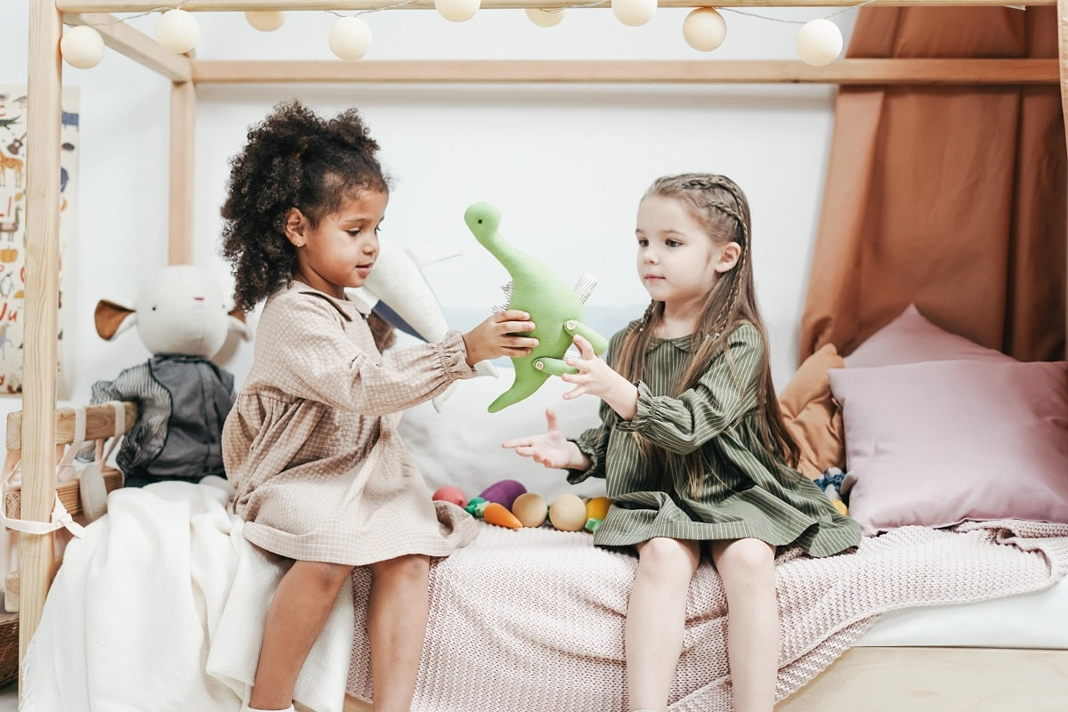Two girls sitting on a bed playing with a stuffed toy.